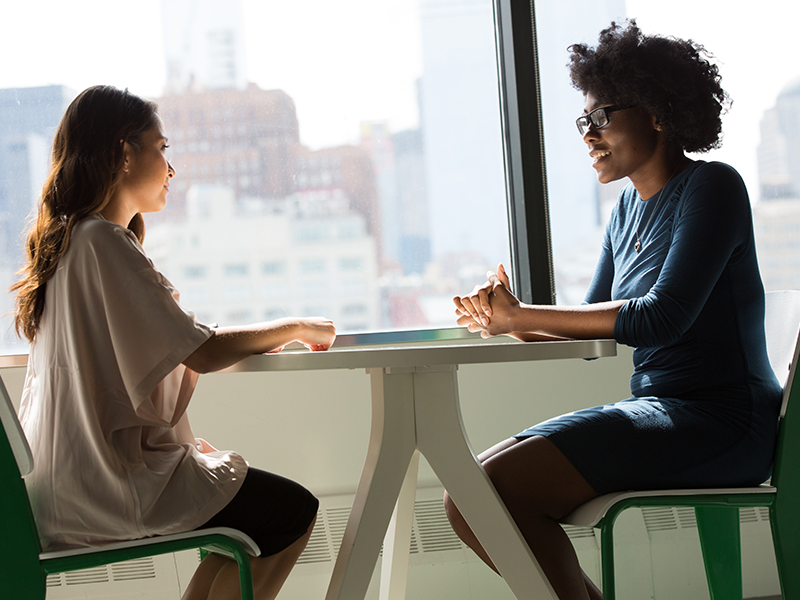 Two women sitting around a small rounded able, having a conversation